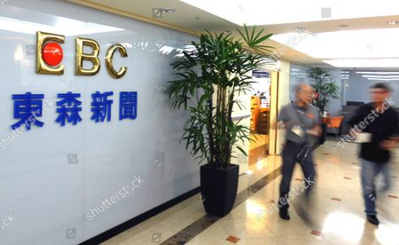Two Eastern Broadcasting Corp (ebc) Staff Members Walk Past the Logo of Ebc in a Building in Taipei Taiwan 23 November 2015 on 23 November Taiwan Said It Would Block Us Firm Dmg Entertainment's Buying Stake in Ebc if the Stake is Over 50 Per Cent and if Dmg is Linked with China's Military a Day Earlier Dmg Ceo Dan Mintz Told the Los Angeles Times That He Had Agreed to Buy 61 Per Cent of Carlyle Group's Stake in Ebc For Us$600 Million So As to Boost Airing of Dmg's Chinese Content Programmes the News Triggered Strong Reaction From the Opposition Democratic Progressive Party Saying It was Firmly Opposed to the Sale Fearing China's Control of Taiwan Media and Encroachment on Freedom of Speech Ebc Called Dongsen Tv in Chinese Has Several Channels Broadcasting News and Entertainment Programmes in Taiwan Southeast Asia and the Us Taiwan Taipei