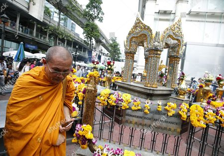A Buddhist Monk Walks Past a Statue of Lord Brahma the Hindu God of Creation at the Erawan Shrine in Bangkok Thailand 22 September 2015 Tourism Authority of Thailand (tat) Invitation Hong Kong Superstars Michelle Yim Also Known As Mai Suet and Simon Yam Tak-wah Visited the Erawan Shrine on 22 September to Help Restore the Confidence of Chinese Tourists Hong Kong and Thai Tourism Industry After a Bombing on 17 August That Killed at Least 20 People and Injured More Than Hundred Thailand Bangkok