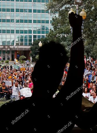 """Stock Photo of Sabrina Carter, with the workers advocacy group Stand With Dignity, raises her fist as she completes a speech at an """"Anti-Trump Inauguration Rally and March"""" across from the City Hall in New Orleans, . Donald J. Trump was sworn in as the 45th President of the United States, Friday"""
