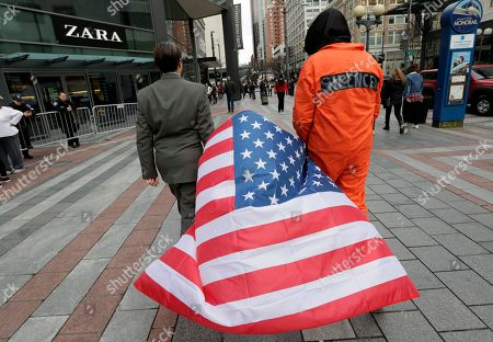 Kieran Harrison, left, and another man who declined to be identified, walk away with a flag they had been standing on during a 45-minute silent street theater protest marking Inauguration Day, in Seattle. They said that the juxtaposition of a suited man and another in prison garb symbolized the friction between the power of financial elite with that of the will of the mass of people governed by it