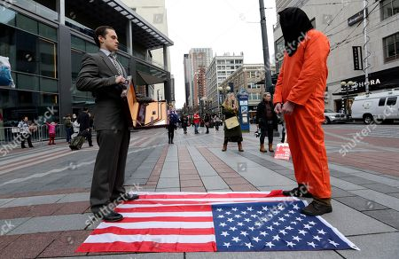 Kieran Harrison, left, and another man who declined to be identified, stand during a silent street theater protest marking Inauguration Day, in Seattle. They said that the juxtaposition of a suited man and another in prison garb symbolized the friction between the power of financial elite with that of the will of the mass of people governed by it