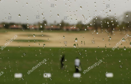 Camilo Villegas hits on the driving range as rain begins to fall during the second round of the CareerBuilder Challenge golf tournament on the Jack Nicklaus Tournament Course at PGA West, in La Quinta, Calif