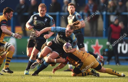 Stock Photo of Kristian Dacey of Cardiff Blues is tackled by Rob Hawkins of Bristol.