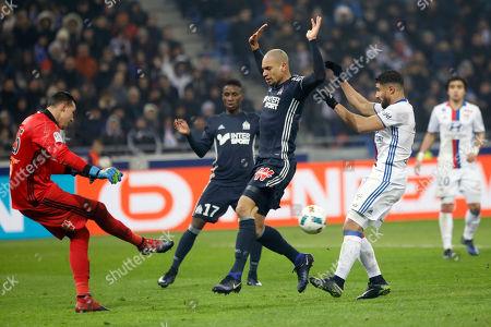 Marseille's goalkeeper Yohann Pele, left, kicks the ball during their French League One soccer match against Lyon, in Decines, near Lyon, central France