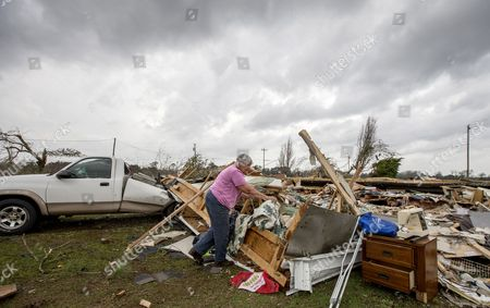 Stock Photo of Ann Bell rests from salvaging possessions from what's left of her son's home after an apparent tornado destroyed it before her son was dug out of the debris by neighbors at 3 am in the Maryville community outside Thomasville, Georgia, USA on 22 January 2017. Emergency officials report that at least eleven people have been killed in Georgia during a severe weather outbreak in the southern United States.