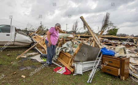 Ann Bell salvages possessions from what's left of her son's home after an apparent tornado destroyed it before her son was dug out of the debris by neighbors at 3 am in the Maryville community outside Thomasville, Georgia USA on 22 January 2017. Emergency officials report that at least eleven people have been killed in Georgia during a severe weather outbreak in the southern United States.