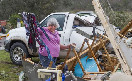 Ann Bell salvages possessions from what's left of her son's home after an apparent tornado destroyed it before her son was dug out of the debris by neighbors at 3 am in the Maryville community outside Thomasville, Georgia, USA on 22 January 2017. Emergency officials report that at least eleven people have been killed in Georgia during a severe weather outbreak in the southern United States.