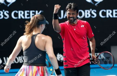 India's Leander Paes, right, celebrates winning a point with Switzerland's Martina Hingis during their mixed double match against Croatia's Nikola Mektic and Brian Baker of the United States at the Australian Open tennis championships in Melbourne, Australia