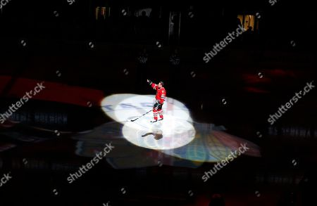 Former Chicago Blackhawks player Jeremy Roenick acknowledges the crowd after being honored before an NHL hockey game between the Vancouver Canucks and the Blackhawks, in Chicago