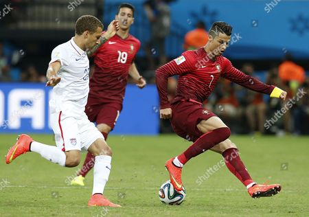 Stock Photo of Fabian Johnson of the Usa (l) and Cristoano Ronaldo of Portugal in Action During the Fifa World Cup 2014 Group G Preliminary Round Match Between the Usa and Portugal at the Arena Amazonia in Manaus Brazil 22 June 2014 (restrictions Apply: Editorial Use Only not Used in Association with Any Commercial Entity - Images Must not Be Used in Any Form of Alert Service Or Push Service of Any Kind Including Via Mobile Alert Services Downloads to Mobile Devices Or Mms Messaging - Images Must Appear As Still Images and Must not Emulate Match Action Video Footage - No Alteration is Made to and No Text Or Image is Superimposed Over Any Published Image Which: (a) Intentionally Obscures Or Removes a Sponsor Identification Image; Or (b) Adds Or Overlays the Commercial Identification of Any Third Party Which is not Officially Associated with the Fifa World Cup) Brazil Manaus