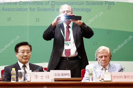 German Md Volker Ter Meulen (c) Standing Between an Unidentified Man and Canadian Nobel Laureate Robert Mundell (r) Snaps a Photo Before the Start of the Nobel Laureates Beijing Forum Held at the Great Hall of the People in Beijing China 10 September 2013 the Theme of This Year's Strategic Forum is 'New Materials and Energy ' Guests of the 2013 Forum Include Nobel Laureates Edmund Phelps George Smoot James Mirrlees Robert Mundell As Well As Four Renowned Scientists China Beijing