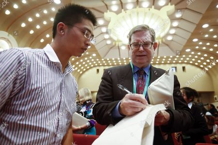 Stock Image of Us Nobel Laureate George Smoot (r) Signs an Autograph For a Chinese Student During the Nobel Laureates Beijing Forum Held at the Great Hall of the People in Beijing China 10 September 2013 the Theme of This Year's Strategic Forum is 'New Materials and Energy ' Guests of the 2013 Forum Include Nobel Laureates Edmund Phelps George Smoot James Mirrlees Robert Mundell As Well As Four Renowned Scientists China Beijing