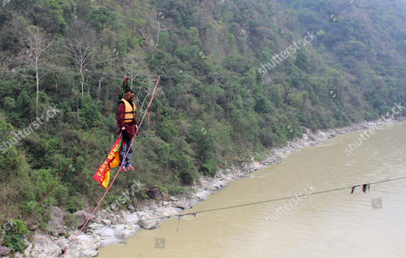 Indian Guinness World Record Holder Sailendra Nath Roy 50 Hangs on a Rope From His Pony Tail During an Attempt to Try to Cross the River Teesta with a Rope Tied Between Two Hills in Sevok on the Outskirts of Siliguri India 28 April 2013 Reports State Roy Died of a Heart Attack During the Attempt After His Pony Tail Got Stuck in the Wheeler on the Rope and He Struggled to Escape For Some 25 Minutes Sailendra Nath Roy Got His Name in the Guinness Book of Records by Pulling the Heritage Darjeeling Himalayan Toy Train in September 2012 India Siliguri