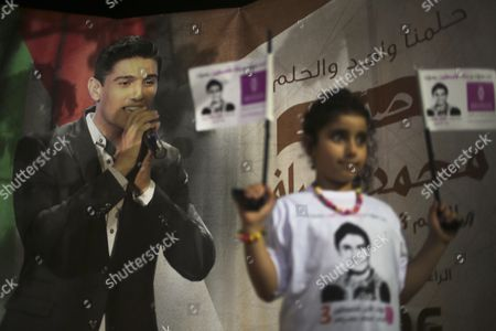 A Young Fan (r) of Palestinian Singer Mohammad Assaf Wearing a T-shirt Depicting the Singer Celebrates That Assaf Won the Arab Idol Talen Tv Show During an Outdoor Event in North Gaza Strip Late 22 June 2013 on the Backgorung a Poster of the Arab Idol Competition Palestinian Singer Mohammad Assaf Reports State That Since March 2013 Mohammad Assaf is Gaza's Powerful Voice Palestinians Watch Him Every Weekend in a Beirut-based Competition That Started out with 27 Contestants - Gaza Strip