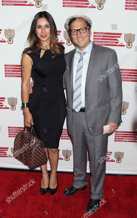 Stock Photo of Us Producer Patricia Azarcoya Schneider and Us Actor Rob Schneider Arrive For the American Friends of the Israel Philharmonic Orchestra Benefit at the Wallis Annenberg Center For the Performing Arts in Beverly Hills California Usa 16 July 2014 the American Friends of the Israel Philharmonic Orchestra Honored German Composer Hans Zimmer with a Lifetime Achievement Award United States Beverly Hills