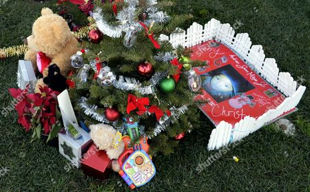 christmas theme decorations and gifts adorn the grave of a boy at the inglewood park cemetery - Christmas Grave Decorations