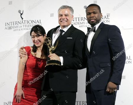 Stock Photo of Miho Yamamoto (l) and Damon Vignale (c) of Canada Stand with Singer Curtis '50 Cent' Jackson (r) While Posing with Their International Emmy Award in the 'Arts Programming' Category For 'The Exhibition' During the 42nd International Emmy Awards Gala in New York New York Usa 24 November 2014 United States New York