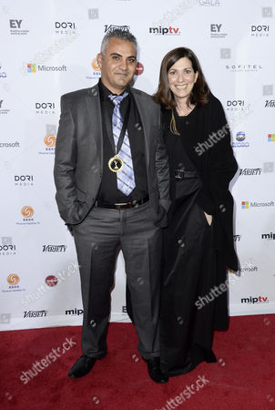 Stock Picture of Emad Burnat Director (l) and Christine Camadessus Producer of the French Documentary '5 Broken Cameras' Arrive For the 41st International Emmy Awards Gala Held at the Hilton Hotel in New York New York Usa 25 November 2013 United States New York