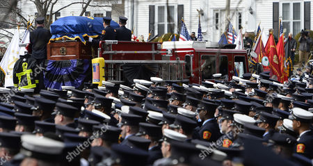 Thousands of Firefighters Stand at Attention As Boston Fire Engine 33 Transports the Casket Following the Funeral For Boston Fire Lt Edward Walsh in Watertown Massachusetts Usa 02 April 2014 Walsh and Firefighter Michael Kennedy Were Killed in a Fire in the Back Bay Section of Boston 26 March 2014 United States Watertown