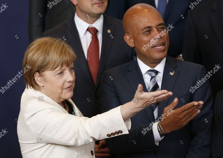 German Chancellor Angela Merkel (l) and Haitian President Michel Joseph Martelly (r) Chat During a Family Picture at the European Union and Community of Latin American and Caribbean States (celac) Summit in Brussels Belgium 10 June 2015 the Eu-celac Summit Brings Together 61 European Latin American and Caribbean Leaders to Strengthen Relations Between Both Regions Belgium Brussels
