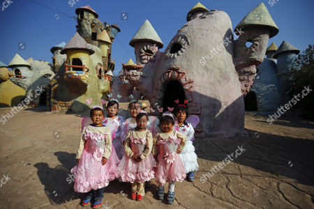 (l-r) 'Dwarf Empire' Cast Members Zhu Hui Peng Chun Song Han Zhen Yan Liu Jin Jin Chen Jian Quan and Liu Ke Gang Pose in Their Fairy Costumes Backstage in Front of Fairy Tale-like Houses Before Going on Stage at the Dwarf Empire Theme Park Outside Kunming China's Yunnan Province 04 April 2013 the Dwarf Empire Theme Park Opened in Mid-2009 Employing a Number of Dwarves to Create the Show Depending on what Type of Job They Do at the Park Employees Earn Between 800-2 000 Cny (100-250 Euros) Per Month Most of Which Goes Towards Their Savings As Lodging is Provided and Their Living Quarters Are Equipped with Kitchens where They Prepare Their Own Meals China Kunming