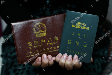 A Picture Made Available on 15 April 2015 Shows Zhang Wen Xia a Chinese Woman who Migrated From the Province to Live and Work in Beijing Presenting Her Liaoning Province Hukou (l) Or Household Registration and Beijing Temporary Residence Permit (r) During an Interview with Journalists in Tongzhou District of Beijing China 18 March 2015 in China Most Internal Migrants Encounter Problems Due to the Controversial Household Registration Or 'Hukou' System That Leave Them As 'Temporary Residents' Without Full Access to Welfare Services and Education Opportunities Even Decades After They Move to Other Cities a Program is Reportedly Planned to Be Implemented by Government in 62 Cities and Regions Including Beijing's Tongzhou District in Efforts to Reform the System Under the Scheme 'Anyone Living in the District with a Legitimate Job Will Be Eligible For the Credit System' According to a February Report From China's Official Broadcaster Cctv News Tongzhou Residents Can Earn Credits According to How Many Years They've Been Paying Social Insurance and How Long They've Been Settled in the City the Report Said Without Giving Further Details China Beijing