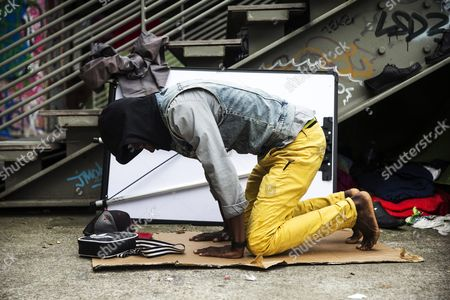 Stock Image of Lybian Migrant Nalaal Prays During the Asr Mid Afternoon Prayer As Part of His Ramadan Observances in the Migrant Camp Located Under the Cit? De La Mode (city of Fashion) Next to the Austerlitz Train Station in the 13th Arrondissement of Paris France 20 June 2015 20 Year Old Nalaal Has Been in France For One Year He Had to Flee Libya to Avoid Imprisonment As His Father was Fighting in the Army of Muammar Al-gaddafi and was Himself a Trainee He is Waiting For His Refugee Status to Be Accepted However Cannot Understand His Living Situation: 'France Waged War on Kadhafi (sic) i Came in France to Find the Land of Equality But This is a Pain' France Paris