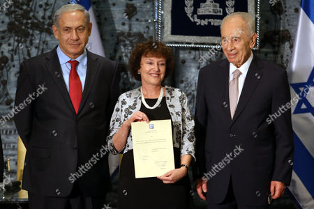 Karnit Flug (c) the New Governor of the Bank of Israel Holds Her Certificate While Being Flanked by Israeli President Shimon Peres (r) and Prime Minister Benjamin Netanyahu (l) During Her Appointment Ceremony at the Israeli President's Residence in Jerusalem 13 November 2013 Karnit Flug is the First Woman to Hold the Position of the Bank of Israel Governor in Israel's History Flug is Replacing Us-israeli Economist Stanley Fischer who Held the Post For the Past Eight Years Flug who Studied at Columbia University New York was Born in Poland in 1955 She Moved to Israel with Her Family As a Toddler Israel Jerusalem