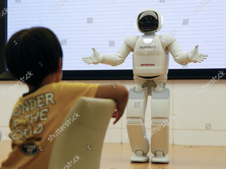 A Boy is Looking at Honda Motor Co 'S Humanoid Robot Asimo at the Headquarters in Tokyo Japan 29 July 2014 Honda Motor Co Said on 29 July 2014 Its Net Profit For the April-to-june Quarter Jumped 19 6 Percent From a Year Earlier to 146 5 Billion Yen (1 44 Billion Us Dollar) Due Mainly to Cost-cutting Measures and Robust Sales in Japan and Other Asian Markets Japan's Third-largest Carmaker Said Its Operating Profit For the Quarter Grew 7 1 Percent From the Same Period Last Year to 198 Billion Yen While Sales Were Up 5 4 Percent to 2 99 Trillion Yen Japan Tokyo
