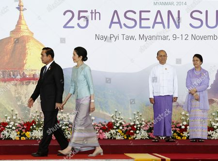 Thailand Prime Minister Prayut Chan-o-cha (l) Holds the Hand of His Wife Naraporn Chan-o-cha As They Walk Towards the Opening Ceremony After Having Been Greeted by Myanmar President Thein Sein (2-r) and His Wife Khin Khin Win (r) For the Start of the 25th Association of South East Asian Nations (asean) Summit at the Myanmar International Convention Centerin Naypyitaw Myanmar 12 November 2014 South-east Asian Leaders Gathered in Myanmar's Capital Naypyidaw on 12 November For the Bi-annual Asean Summit with the Focus Expected to Be on Economic Ties and Regional Territorial Disputes the Final Provisions of the Asean Economic Community - Due to Be Completed in December 2015 - Will Be High on the Agenda of the Two-day Conference the 10 Member Countries Will Also Be Launching a Green Economy Initiative to Combat Global Warming Asean Comprises Brunei Indonesia Malaysia the Philippines Singapore Thailand Vietnam Cambodia Laos and Myanmar the Asean Meetings Will Also Include Leaders From South Korea Australia New Zealand and Russia Myanmar Naypyitaw