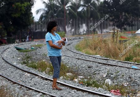 A Filipino Mother Carrying a Baby Walks on Deserted Train in Manila Philippines 19 March 2015 State-owned Train System Philippine National Railway (pnr) Will Upgrade Its Railways and Locomotives Through Partnership with American Based Companies Miescorrail Desco and General Electric (ge) According to United States Embassy Trade Commissioner Jim Mccarthy the Rehabilitation of Pnr is the First Major Upgrade Since Its Acquisition and Signified the Renewal of Business Ties Between the Philippines and the Us Mccarthy Added Philippines Manila