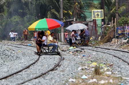 Filipinos Ride on a Makeshift Pushcart Along Train Tracks in Manila Philippines 19 March 2015 State-owned Train System Philippine National Railway (pnr) Will Upgrade Its Railways and Locomotives Through Partnership with American Based Companies Miescorrail Desco and General Electric (ge) According to United States Embassy Trade Commissioner Jim Mccarthy the Rehabilitation of Pnr is the First Major Upgrade Since Its Acquisition and Signified the Renewal of Business Ties Between the Philippines and the Us Mccarthy Added Philippines Manila