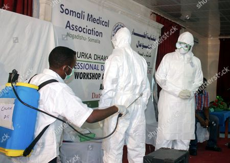 Stock Photo of A Somali Instructor (r) Demonstrates How to Decontaminate the Suits Worn by Those Treating Ebola Patients to Participants During an Ebola Awareness Event Held by the Somali Medical Association in Mogadishu Somalia 24 October 2014 Local Media Reported That Somalia's Prime Minister Abdiweli Sheikh Ahmed Has Ordered Government Agencies to Step Up Its Effort to Prevent Ebola From Entering the Country As Mali Has Its First Confirmed Case of the Disease and the African Union (au) 23 October Said That It Will Send More Than 1 000 Health Workers to the West African Nations of Liberia Sierra Leone and Guinea All Suffering Heavily From the Outbreak of Ebola to Combat the Epidemic Somalia Mogadishu