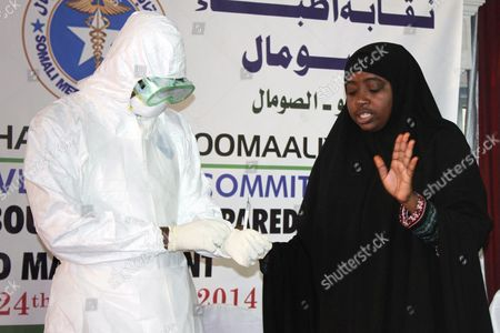 Stock Image of A Somali Doctor (r) Demonstrates the Protective Suits Worn by Those Treating Ebola Patients to Participants During an Ebola Awareness Event Held by the Somali Medical Association in Mogadishu Somalia 24 October 2014 Local Media Reported That Somalia's Prime Minister Abdiweli Sheikh Ahmed Has Ordered Government Agencies to Step Up Its Effort to Prevent Ebola From Entering the Country As Mali Has Its First Confirmed Case of the Disease and the African Union (au) 23 October Said That It Will Send More Than 1 000 Health Workers to the West African Nations of Liberia Sierra Leone and Guinea All Suffering Heavily From the Outbreak of Ebola to Combat the Epidemic Somalia Mogadishu