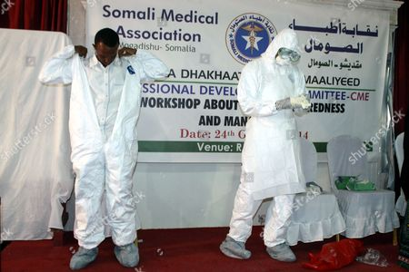 Stock Picture of Two Somali Instructors Demonstrate Putting on the Protective Suits Worn by Those Treating Ebola Patients to Participants During an Ebola Awareness Event Held by the Somali Medical Association in Mogadishu Somalia 24 October 2014 Local Media Reported That Somalia's Prime Minister Abdiweli Sheikh Ahmed Has Ordered Government Agencies to Step Up Its Effort to Prevent Ebola From Entering the Country As Mali Has Its First Confirmed Case of the Disease and the African Union (au) 23 October Said That It Will Send More Than 1 000 Health Workers to the West African Nations of Liberia Sierra Leone and Guinea All Suffering Heavily From the Outbreak of Ebola to Combat the Epidemic Somalia Mogadishu