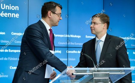 Latvia's Finance Minister Janis Reirs (l) and European Commission Vice-president in Charge of the Euro and Social Dialogue Valdis Dombrovskis (r) of Latvia Shake Hands at a Joint News Conference at the End of European Finance Ministers Meeting at Eu Council Headquarters in Brussels Belgium 27 January 2015 Belgium Brussels