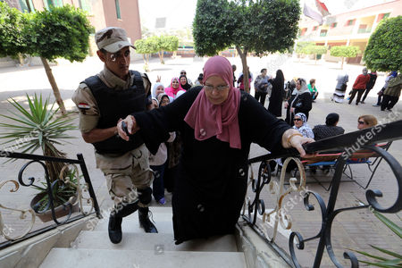 An Egyptian Soldier Helps a Woman As She Enters a Polling Station During the Presidential Elections at a Polling Station in Heliopolis District Cairo Egypt 26 May 2014 Egyptians Began on 26 May Two Days of Voting to Elect a New President in the First Elections Since the Army Deposed Islamist President Mohamed Morsi More Than 11 Months Ago the Election is a Two-man Race Between Former Army Chief Abdel Fattah Al-sisi and Leftist Politician Hamdeen Sabahi Egypt Cairo