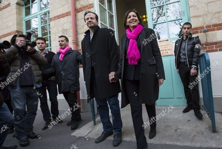 Anne Hidalgo (r) the Parti Socialist (ps) Political Party Candidate For Paris' 2014 Municipal Election and Her Partner Jean-marc Germain (l) Exit a Polling Station After Casting Their Vote During the First Round of the 2014 Municipal Election in Paris France 20 March 2014 in Paris the Race Pits Outgoing Socialist Mayor Bertrand Delanoe's Deputy Anne Hidalgo Against Former Environment Minister Nathalie Kosciusko-morizet of the Centre-right Union For a Popular Movement (ump) France Paris