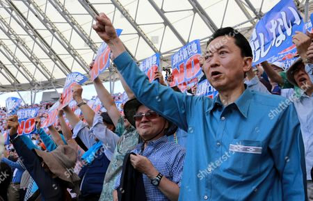 Former Japanese Prime Minister Yukio Hatoyama Attents a Protest Against the Construction of a New Base at Henoko in Nago Coastal Area of the Japanese Southwestern Island of Okinawa at a Baseball Stadium in Naha Okinawa Island Southwestern Japan 17 May 2015 About 35 000 People Participated in the Rally According to Organizers Japan's and the Us Governments Plan to Relocate Us Marine Corps Futenma Air Station in Ginowan a Densely Populated Area to the Coastal Area of Nago on Okinawa Island the Blue Placard Read 'Resist' and the White Ones Read 'Crush Japan-us Security Treaty' Japan Naha