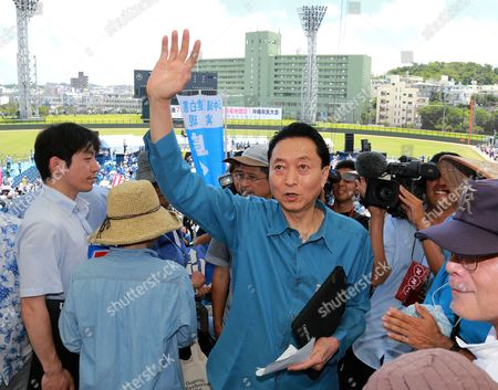 Former Japanese Prime Minister Yukio Hatoyama Waves As He Attents a Protest Against the Construction of a New Base at Henoko in Nago Coastal Area of the Japanese Southwestern Island of Okinawa at a Baseball Stadium in Naha Okinawa Island Southwestern Japan 17 May 2015 About 35 000 People Participated in the Rally According to Organizers Japan's and the Us Governments Plan to Relocate Us Marine Corps Futenma Air Station in Ginowan a Densely Populated Area to the Coastal Area of Nago on Okinawa Island the Blue Placard Read 'Resist' and the White Ones Read 'Crush Japan-us Security Treaty' Japan Naha