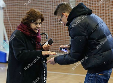 A Member of an Election Commission Checks a Voter's Fingers with an Ultra-violet Light Before Voting in Pristina Kosovo 01 December 2013 Some 1 3 Million Voters Are Called to Take Part on the Second Round of Municipality Elections to Elect Mayors Including Capital Pristina and Four Serb Municipalities in Northern Kosovo Serbia and Montenegro Pristina