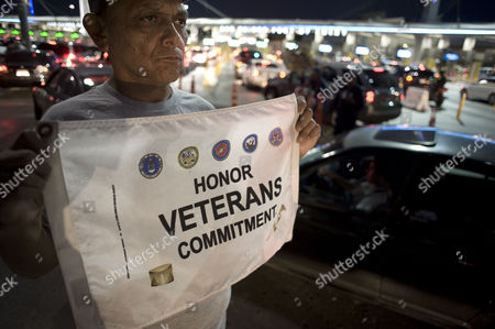 United States Army Veteran Ricardo Avila Torres 59 who Had Been Deported to Mexico in 1996 Holds a Small Banner For Drivers to See During a Protest on Veteran's Day at the Us-mexico Border Vehicle Crossing in Tijuana Mexico 11 November 2014 the Protestors Were Demanding Reform to Immigration Laws That Would Allow Them to Receive Benefits While in Mexico and to Also Allow Them to Seek Re-entry to the United States Avila Served in Vietnam Mexico Tijuana