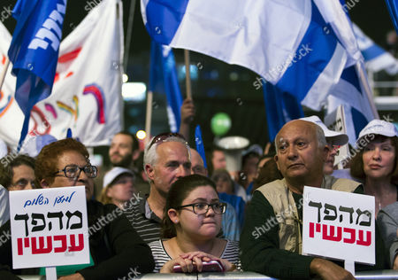 Israelis Listening to a Speech by Former Mossad Chief Meir Dagan at the Huge Rally in Rabin Square in Tel Aviv Israel 07 March 2015 Under the Banner ' Israel Needs Change ' Calling For a Regime Change in Israeli Politics For the March 17 General Election the Small Placards Roughly Translate to 'Evolution Now' and Are a Take-off on the Logo of 'Peace Now ' Israel Tel Aviv