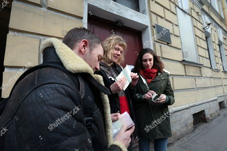 Greenpeace International Activists Phiip Ball (l) Alexandra Harris (r) of the United Kingdom and Sini Saarela of Finland Show Journalists Their Passports in Front of the Federal Migration Service in St Petersburg Russia 26 December 2013 where They Received Russian Transit Visa Criminal Charges Have Been Dropped Against All 30 Crew Members of Greenpeace Ship Arctic Sunrise who Were Arrested After a Protest at an Oil Rig the Environmental Group Said Russian Federation St. Petersburg
