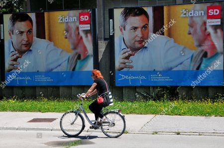 Cyclist Passing the Billboard Advertising Sd (social Democrats) Party and Leader Dejan Zidan in Ljubljana Slovenia 9 July 2014 the Sd was a Part of the Desolved Slovenian Coalition Government the Party Motto 'Dejanje' Means 'Action' Slovenia Ljubljana