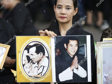 A Mourner Holds Photographs of the Late Thai King Bhumibol Adulyadej (l) and Bhutan King Jigme Khesar Namgyel Wangchuck (r) As She Waits to Pay Respects to the Late Thai King Outside the Grand Palace in Bangkok Thailand 16 October 2016 King Bhumibol the World's Longest Reigning Monarch Died at the Age of 88 in Siriraj Hospital on 13 October 2016 Thailand Bangkok