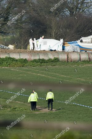 Police Forensic Experts in White Protection Suits Examine the Wreckage of a Helicopter at the Accident Site in Gillingham Norfolk Britain where a Civilian Helicopter Crashed Reportedly Killing All Four Occupants 14 March 2014 Lord Ballyedmond One of the Richest Men in Northern Ireland was Among Four People who Have Died in a Helicopter Crash Near the East Coast of England British Media Reported Friday the Agustawestland Aw139 Came Down in a Field Near the Village of Gillingham During Thick Fog Late Thursday Police Said the Victims Had not Yet Been Formally Identified and It was not Clear what Caused the Crash Ballyedmond Edward Haughey Before He was Created a Life Peer in 2004 was Chairman of Norbrook the Largest Privately Owned Pharmaceutical Company in the World He Had Served in Both the British and Irish Upper Houses of Parliament United Kingdom Gillingham