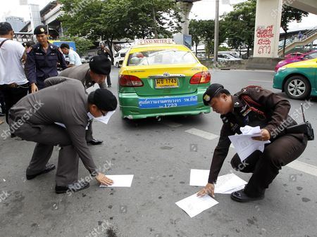 Thai Police Officers Pick Up Leaflets Against Military Junta Thrown by a Protester on a Street Outside Chatuchak Market in Bangkok Thailand 31 August 2014 at Least Three People Were Arrested During a Demonstration After a Thai Criminal Court Dropped the Murder Cases Against Former Prime Minister Abhisit Vejjajiva and His Deputy Suthep Thaugsuban For Authorizing a Crackdown on Anti-government Protesters in 2010 Thailand is Now Under Martial Law Which Prohibits All Political Gatherings of More Than Five People Thailand Bangkok