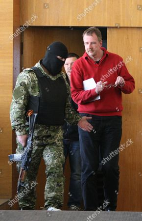 An Unidentified Organization For Security and Cooperation in Europe (osce) Military Observer is Escorted by a Masked and Armed Man During the Osce Observers Presentation to the Media by the So Called People's Mayor of Slaviansk Vyacheslav Ponomarev in Slaviansk Ukraine 27 April 2014 the Seven Observers From Vienna-based Osce Five Ukrainian Officers and One Driver of a Bus Were Detained by Pro-russian Separatists in Eastern Ukrainian on 25 April 2014 and Are Held Captive on Charges of Espionage Ukraine Slaviansk