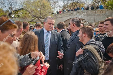 Crimean Premier Sergei Aksyonov (c) Speaks with People who Watch a Tv Broadcast with Russian President Vladimir Putin Speaking During His Annual Call-in Live Broadcast (not Pictured) on the Seafront in Sevastopol Crimea 17 April 2014 the Decision to Send Tanks and Combat Aircraft to Eastern Ukraine is Another Serious Crime Committed by the Authorities in Kiev Putin Said He Called on the Ukrainian Government to Engage in 'Real Dialogue' with Its Russian-speaking Population Adding That the Deployment of 'Military Planes and Tanks' Would not Solve the Crisis in Eastern Ukraine in His Televized Call-in Show Putin Said That Kiev's Decision to Curb the Protests in the Eastern Region of Donetsk with Military Force was a 'Crime ' Ukraine Sevastopol